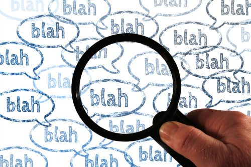 hand holding magnifying glass over speech bubbles containing the words 'blah blah blah'