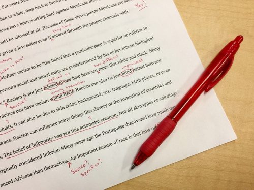 red pen laying on edited paper removing unnecessary words