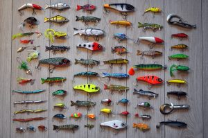 array of fishing hooks and lures arranged on wooden background