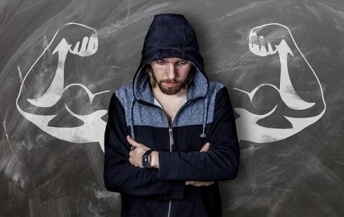 writer thinking of strong words in front of chalkboard drawing of muscular arms