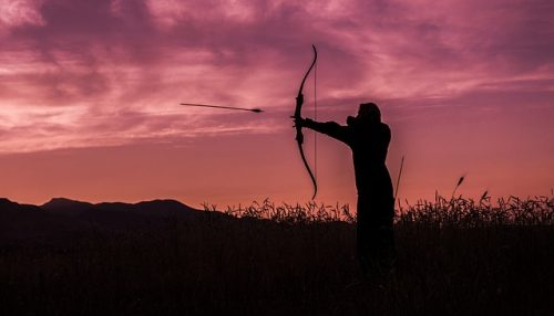 young woman shooting bow at sunset like katniss everdeen
