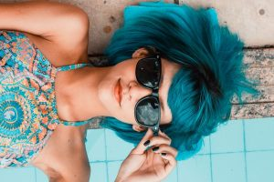 woman with blue hair lounging by pool in sunglasses
