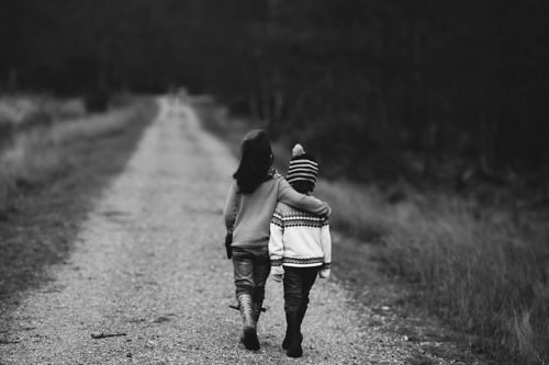 two siblings lovingly embracing while walking down a road