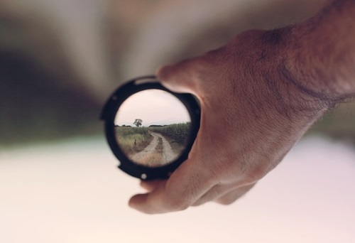 hand holding camera lens focused on a gravel road