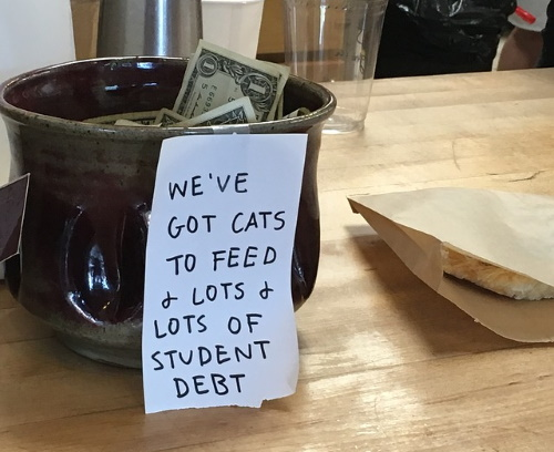 tip jar with note that says 'we've got cats to feed & lots of student debt'