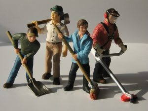 four plastic action figures posing with tools and brooms