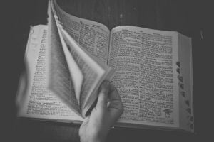 black and white image of hand flipping through dictionary pages
