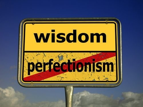 street sign with the word 'wisdom' over 'perfectionism' crossed out
