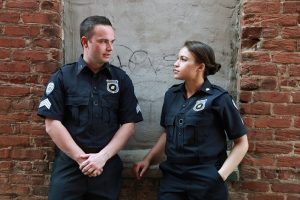 male and female police officers talking in front of brick wall