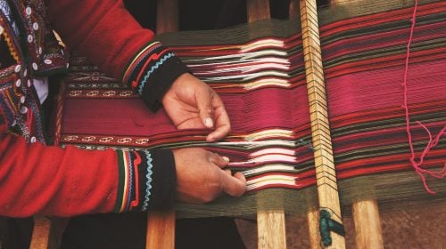 weaver's hands moving threads through loom