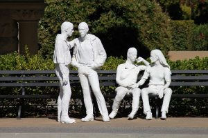 sculpture of a group of men and women discussing opposing viewpoints
