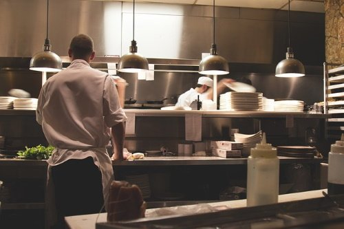 chef synthesizing dishes in a restaurant kitchen