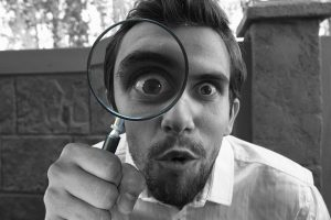 man looking for examples with magnifying glass