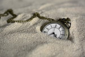 vintage pocket watch partially buried in sand
