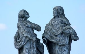 weathered historical statues facing one another
