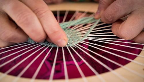 hands weaving blue thread in round loom