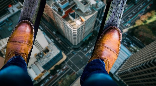 feet balancing on wooden ledge above city