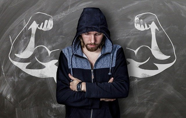 person lacking confidence standing in front of inspirational strength drawing