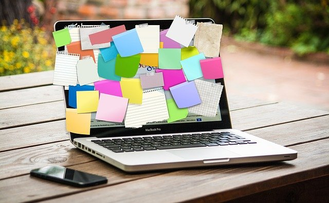 laptop covered in paper sticky notes