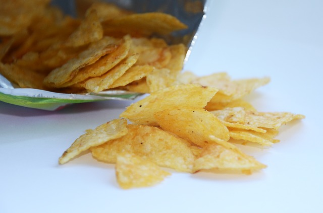 open bag of potato chips spilling onto surface