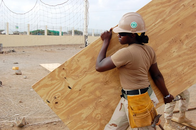 strong black woman carrying plywood on construction site