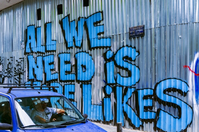 graffiti on sheet metal wall that says 'all we need is more likes'
