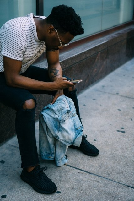 young black person sitting outside looking at phone
