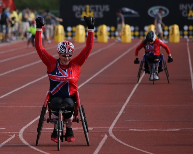 person in wheelchair crossing finish line victoriously