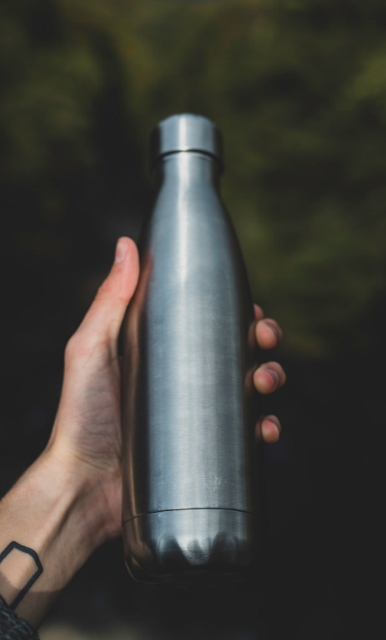 hand holding stainless steel water bottle