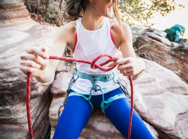 smiling woman tying climbing knot