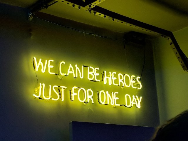 neon sign that says 'we can be heroes just for one day'