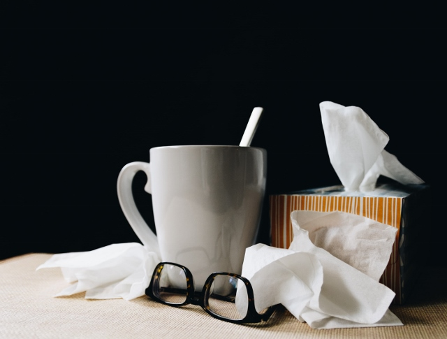 cup of tea, tissues, and glasses for a sick day