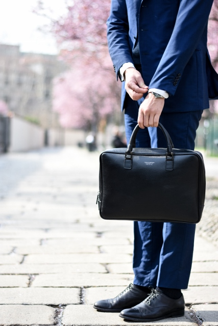 salesman holding briefcase and wearing blue suit