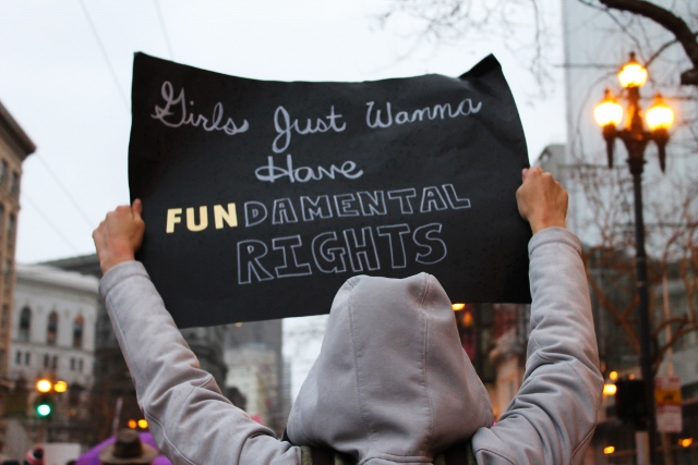 person in hoodie holding sign that says 'girls just wanna have fundamental rights'