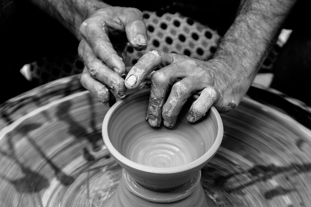 hands shaping pottery on a potter's wheel