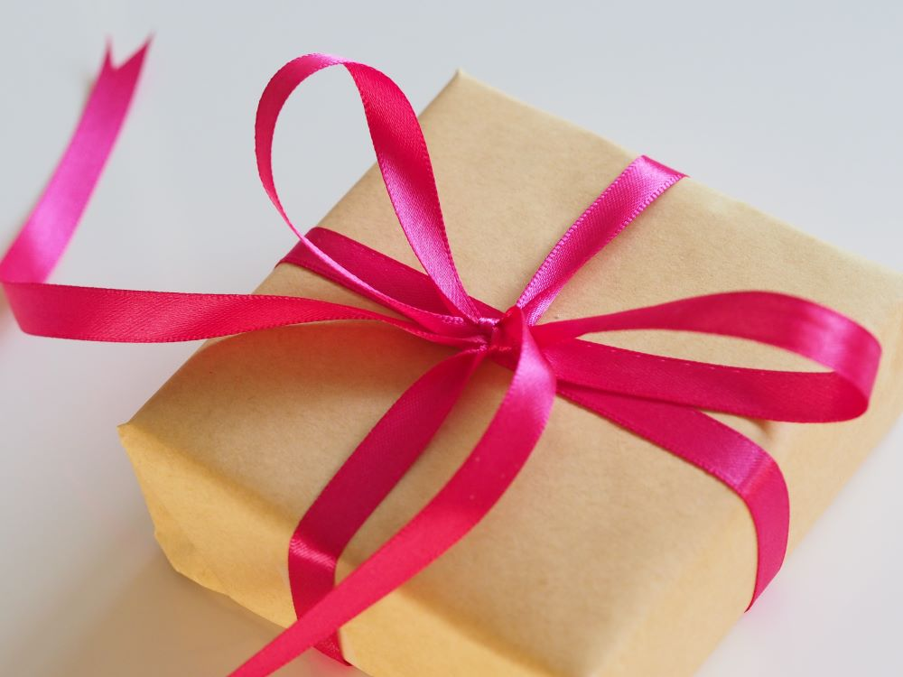 brown box wrapped up with pink ribbon bow